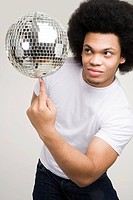 A young man balancing a disco ball