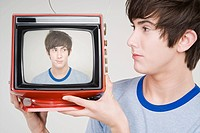 A teenage boy holding a retro tv