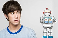 Teenage boy looking at a robot