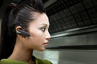 A woman wearing a bluetooth headset