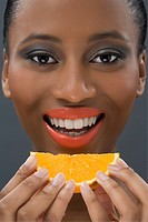 Woman eating a slice of orange
