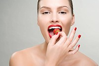 Young woman eating a strawberry