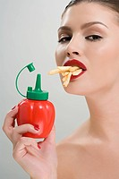 Woman holding tomato ketchup and eating fries