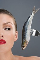 Woman looking at a fish on a fork