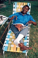 A man with a leg injury sits outdoors.