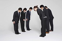 Businesspeople Bowing To Each Other