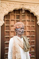 Mature man standing in front of a wooden door, Jaisalmer, Rajasthan, India