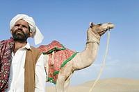 Man standing with a camel in a desert, Thar Desert, Jaisalmer, Rajasthan, India