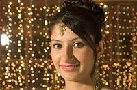 Woman smiling in front of Diwali decoration