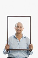 Man holding a picture frame and smiling