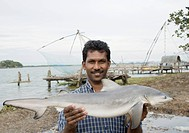 Fisherman showing a fish and smiling, Cochin, Kerala, India