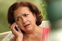Worried Hispanic woman talking on cell phone