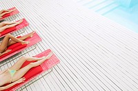 Young Women Sunbathing by pool on deckchairs low section high angle view (thumbnail)