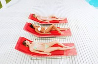 Young women sunbathing on deckchairs by swimming pool high angle view (thumbnail)
