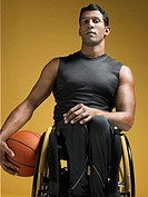 Paraplegic athlete sitting in wheelchair holding basketball