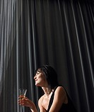 Woman holding champagne in front of curtains indoors