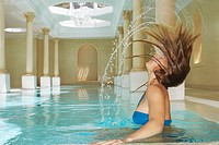 Young woman throwing wet hair back in swimming pool side view