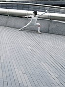 Female fencer lunging outdoors