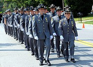 Police officers march down the street at a police funeral in Beltsville, Maryland