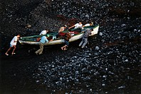 Fishermen shifting boat onto the volcanic beach, Punta de Fuencaliente, La Palma, Canary Islands, Atlantic Ocean, Spain