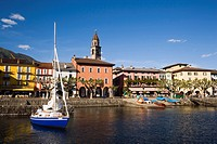 Sailling boat on Lake Maggiore, harbour promenade with spire of church Santi Pietro Paolo in background, Ascona, Ticino, Switzerland