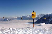 A warning sign in the snow under blue sky, Berchtesgardener Land, Bavaria, Germany