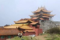 A person sitting in front of Huazang Monastery, Emei Shan mountains, Sichuan province, China, Asia