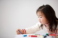 Girl drawing on paper with color pencil