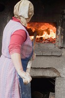 Countrywoman putting bread into a wood_fired oven