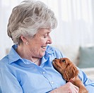 Senior woman hugging puppy