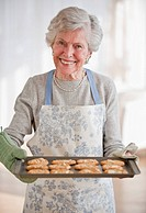 Senior woman holding tray with baked cookies