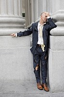 Businessman wearing torn clothing outside office building, San Francisco, California, USA