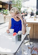 Woman drinking coffee in cafe and talking on cell phone