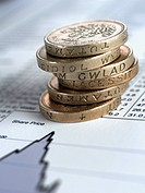 Stack of British pound coins on list of share prices (thumbnail)