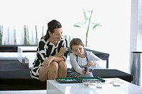 Woman playing backgammon with daughter