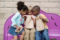 Children looking in friend's lunch bag at recess