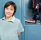 Boy standing near open school locker