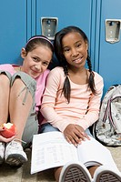 Friends sitting near school lockers in hallway
