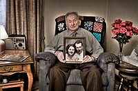 Harry, 103 years old, holds portrait of himself and wife when they were young