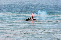Jet ski in distress. The driver of a jet ski lights a distress flare indicating that they are in trouble off the coast of Reunion Island, Indian Ocean...
