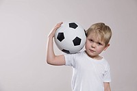 Boy holding soccer ball portrait