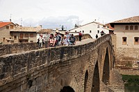 Pilgrims on the St James Way crossing Romanesque bridge at Puente La Reina (Gares), Navarra (Nafarroa), Spain