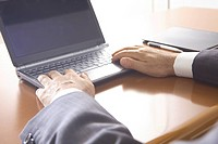 Hands of office worker operating a PC