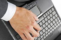 Hand of a man hitting the keyboard of the laptop PC