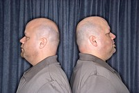Profile of Caucasian bald identical twin mid adult men standing back to back