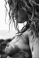 Profile of young adult Caucasian female nude covered in mud