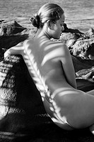 Rear view of Filipino young nude woman sitting on rocky beach