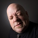 Caucasian mid adult bald man squinting and making facial expression