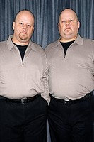 Caucasian bald identical twin mid adult men standing together looking at viewer