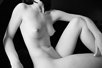 Nude young adult Caucasian female body reclining